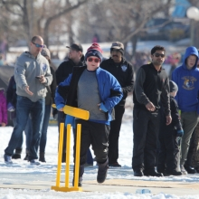 Cavaliers & members of United CC letting boys & girls try cricket (batting) at Waskimo Winter Festival.